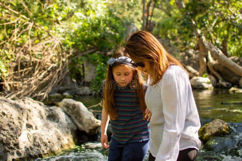 Natureza de explora??o da mulher e da filha junto em um c?rrego ou em um rio imagem de stock royalty free