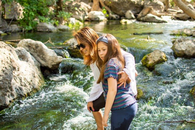 Natureza de explora??o da mulher e da filha junto em um c?rrego ou em um rio fotografia de stock royalty free
