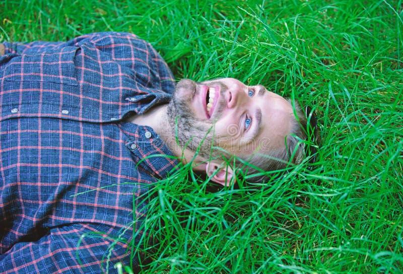 A natureza enche-o com o frescor e a inspiração O indivíduo não barbeado do homem coloca no prado da grama verde Indivíduo feliz  imagens de stock
