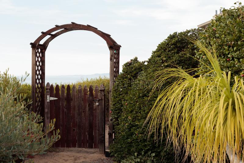 Naturholzpfostentor öffnet sich zur entfernten Ansicht der Gelegenheit oder des Geheimnisses, umgeben durch grünes Laub stockbild