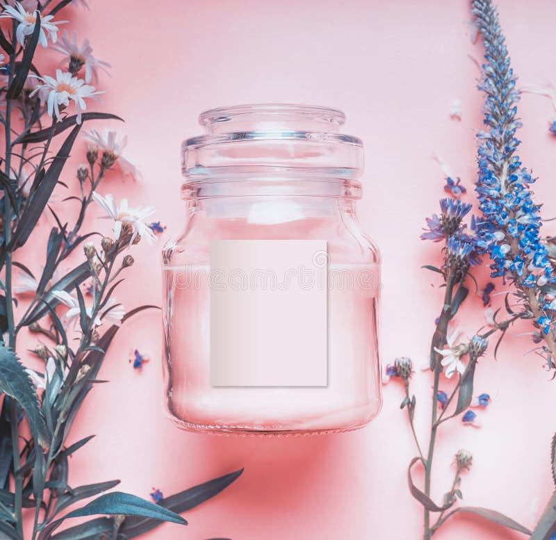 Naturkosmetik rüttelt mit Pastellrosacreme oder Schale, Kräuterblätter und wilde Blumen, Aufkleber des freien Raumes für einbrenn stockfotos
