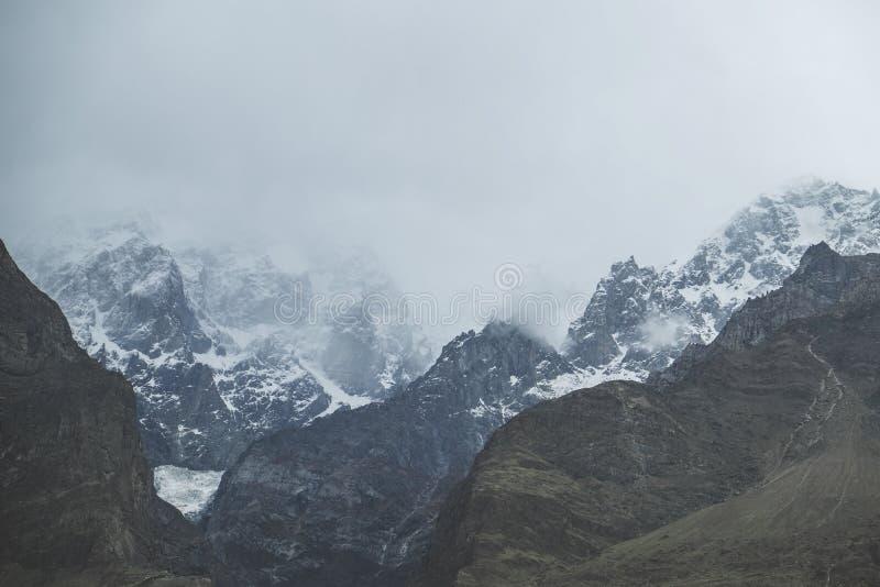 Naturlandskapsikten av moln och dimma täckte det korkade Ultar Sar för snö berget, Pakistan royaltyfri bild