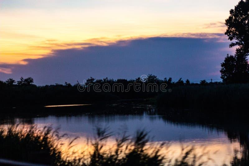 Naturlig bakgrund en flod på soluppgång, reflekterar det färgerna av himlen, medan allt runt om den blir mörkt royaltyfria foton