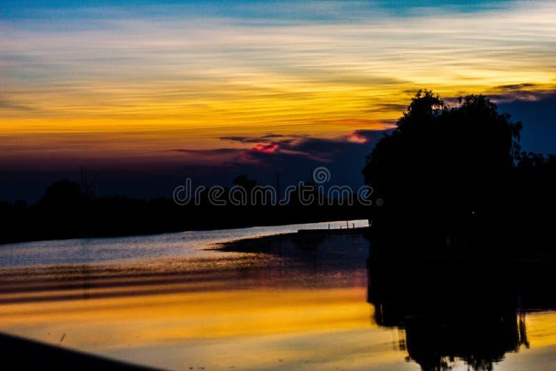 Naturlig bakgrund en flod på soluppgång, reflekterar det färgerna av himlen, medan allt runt om den blir mörkt arkivbild