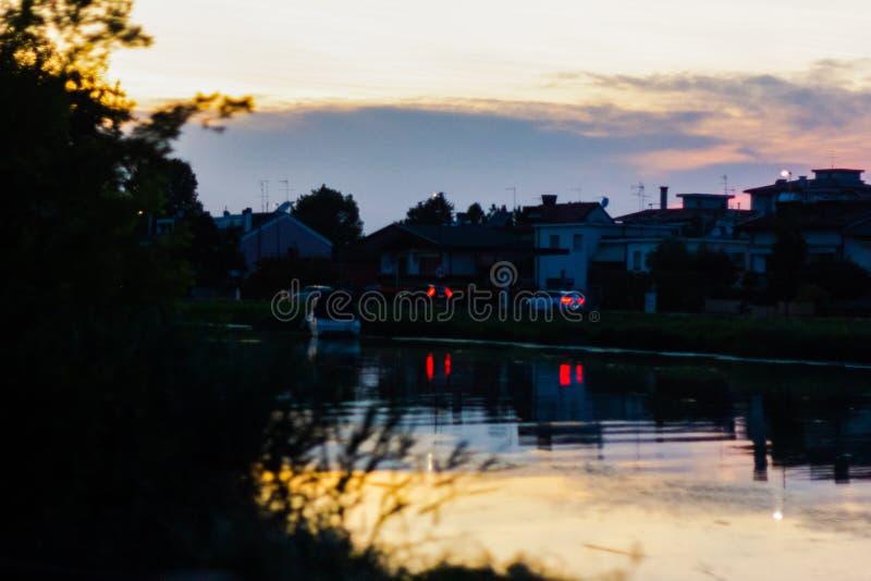 Naturlig bakgrund en flod på soluppgång, reflekterar det färgerna av himlen, medan allt runt om den blir mörkt arkivfoto