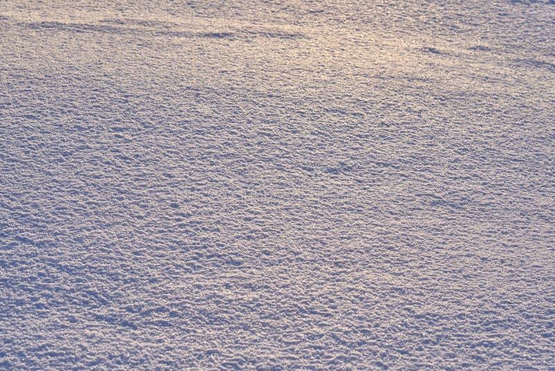 Naturlig bakgrund - isyttersida av snö som är upplyst vid strålarna av aftonsolen Strålarna för sol` som s studsar av det glimma  royaltyfri foto