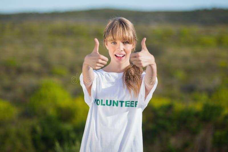 Naturlig blondin som bär en ställa upp som frivillig t-skjorta som ger upp tummar fotografering för bildbyråer