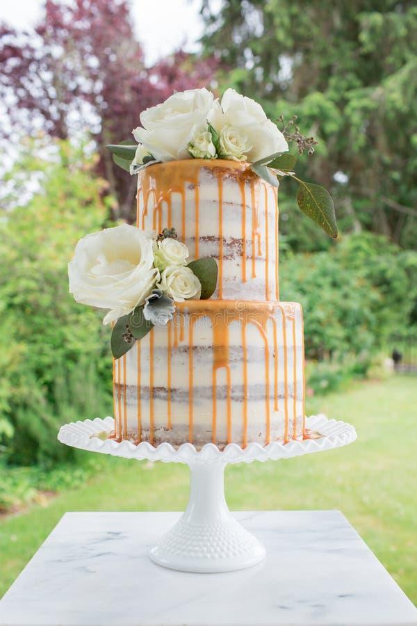 Naturlig bröllopstårta med ingen glasyr på kaka- och karamelldroppandeyttersida royaltyfri bild