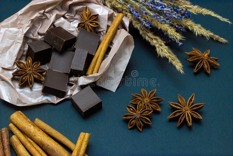 Naturlig choklad med lavendelblommor kanel och stjärnaanis på en mörk bakgrund royaltyfri bild