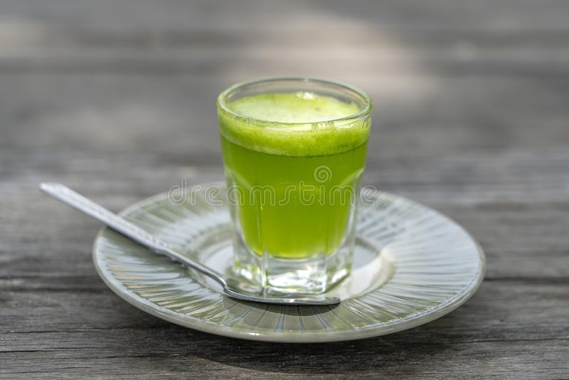 Naturlig drink för vetegräsfruktsaft med nya wheatgrass i exponeringsglas på gammal trätabellbakgrund Organisk sund organisk grön royaltyfri fotografi