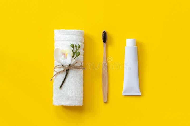 Naturlig eco-vänskapsmatch bambuborste, vit handduk och rör av tandkräm Ställ in för tvätt på pappers- gul bakgrund kopia arkivbilder