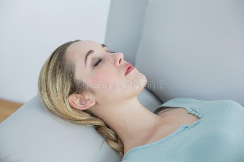 Naturlig fridsam kvinna som ligger på att sova för soffa royaltyfri bild