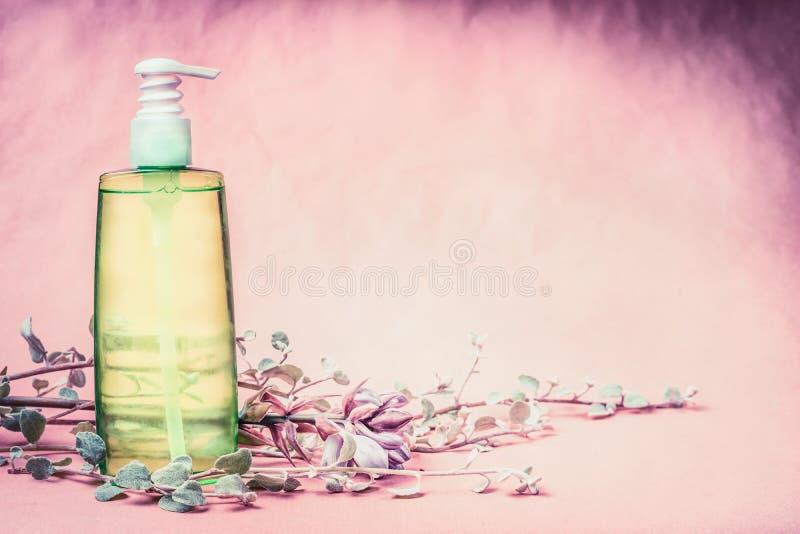 Naturlig kosmetisk produktflaska med grön lotion- eller uppiggningsmedelflytande med nya örter och blommor på rosa bakgrund Sund  arkivfoto