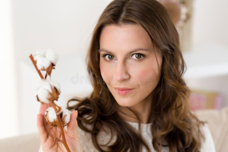 Naturlig kvinna med bomullsblomningen på soffan i hennes vardagsrum royaltyfri fotografi