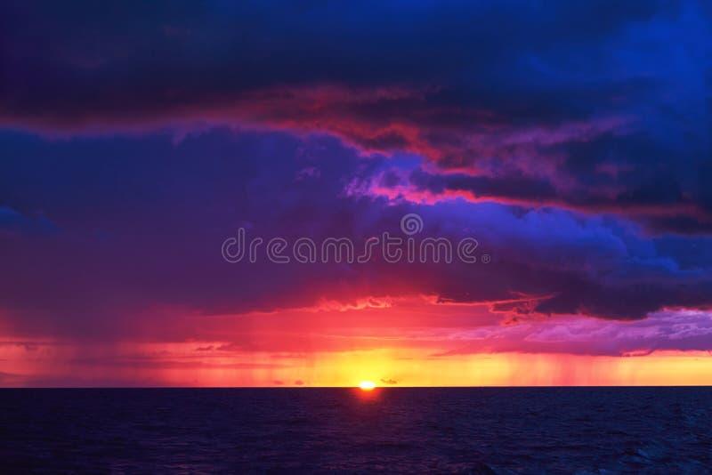 Naturlig lilafärgsolnedgång eller soluppgånghimmel över det stormiga regniga havet royaltyfri foto