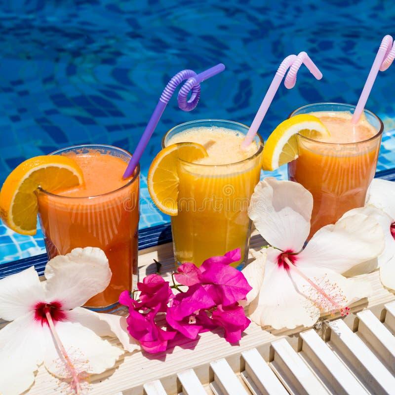 Naturlig ny sammanpressad fruktsaft med stycken av frukt i semesterorten vid pölen royaltyfri foto