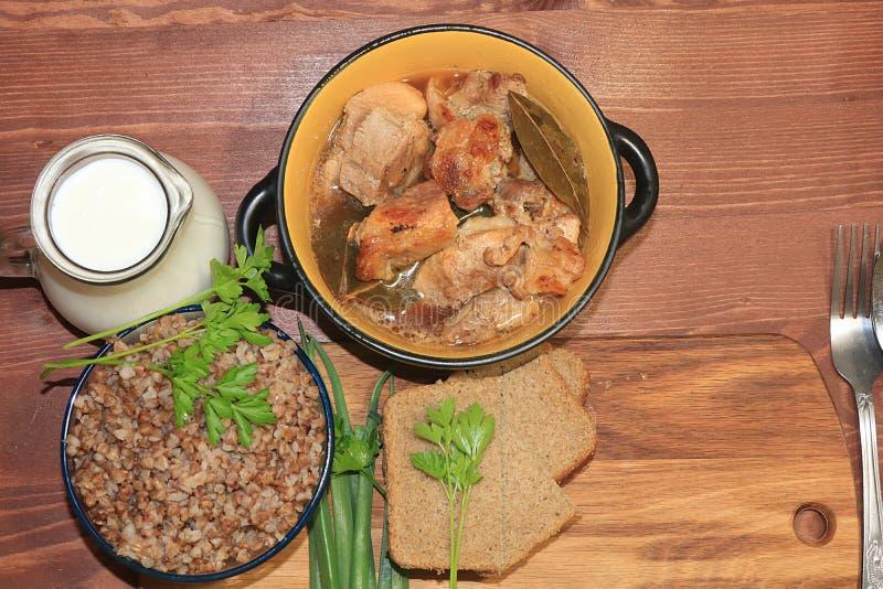 Naturlig organisk bovetehavregröt i en lerakruka, kött i en kruka, en tillbringare av mjölkar och lökar med persilja, en blygsam  royaltyfri bild
