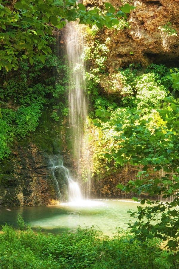 Naturlig romantisk solbelyst vattenfall som faller in i ett litet damm arkivbild
