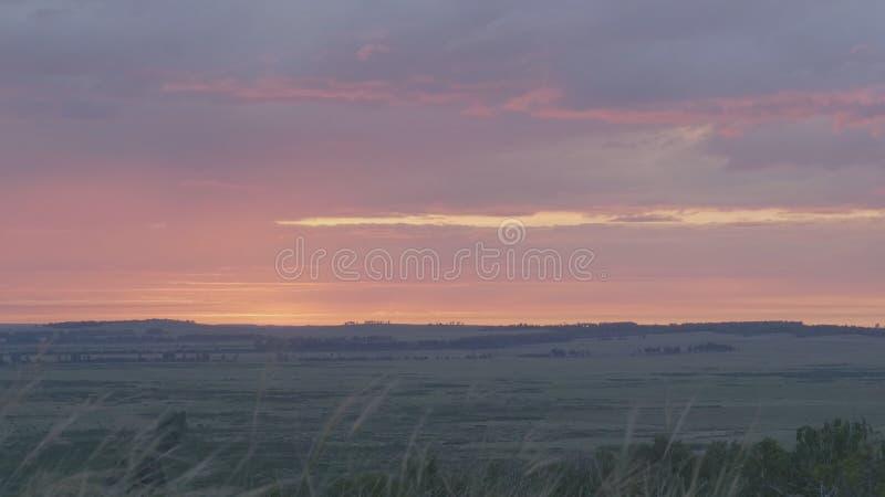 Naturlig soluppgång över fält eller äng Ljus dramatisk himmel och mörkerjordning Bygdlandskap under sceniskt färgrikt arkivfoto