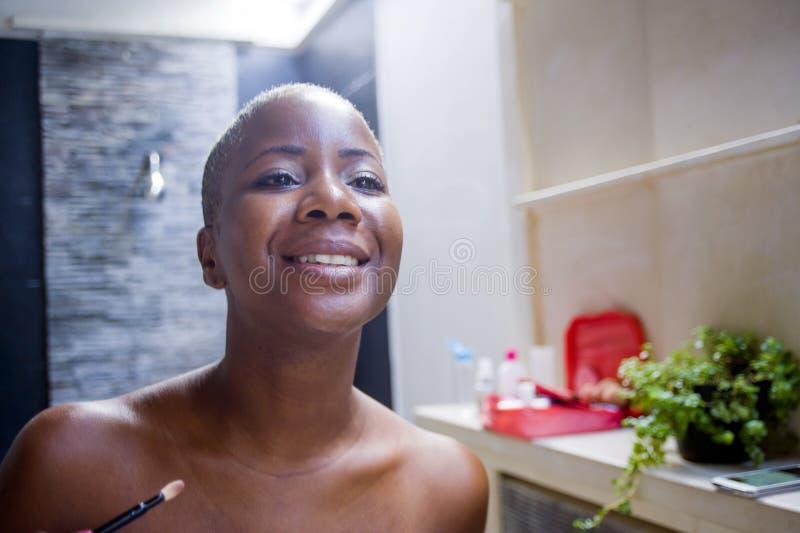 Naturlig stående för livsstil av det unga hemmastadda badrummet för attraktiv och lycklig svart afrikansk amerikankvinna som appl arkivfoto