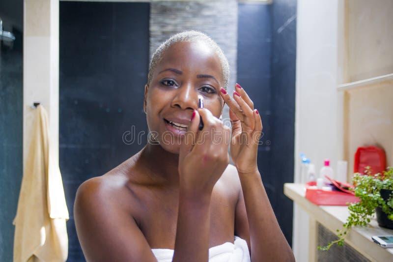 Naturlig stående för livsstil av det unga hemmastadda badrummet för attraktiv och lycklig svart afrikansk amerikankvinna som appl fotografering för bildbyråer