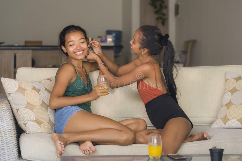 Naturlig stående för livsstil av två kvinnor, en lycklig flicka som tillsammans sätter öracirkeln på hennes unga härliga och exot royaltyfria foton