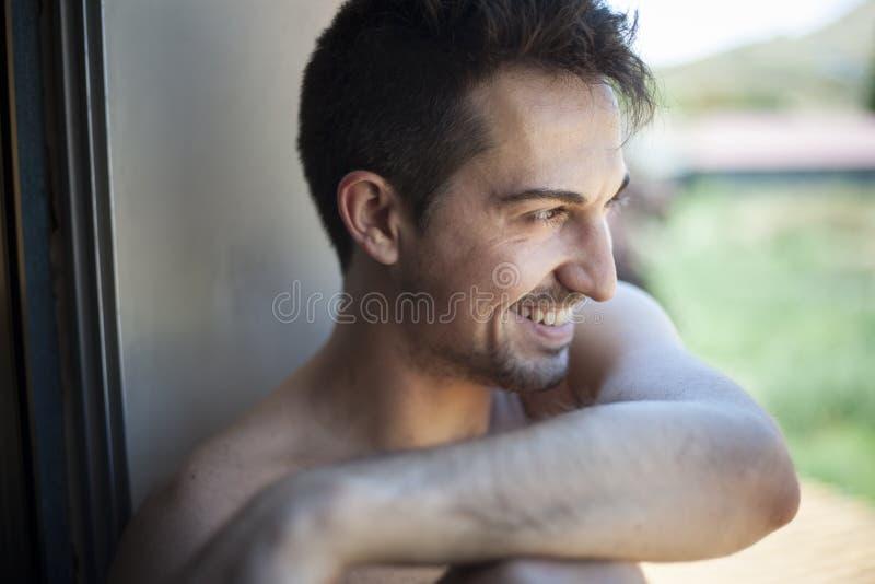 Naturlig stående som skjutas av att le för ung man arkivfoto