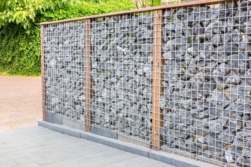 Naturlig trädgårdfäktning med metall och stenar royaltyfri bild