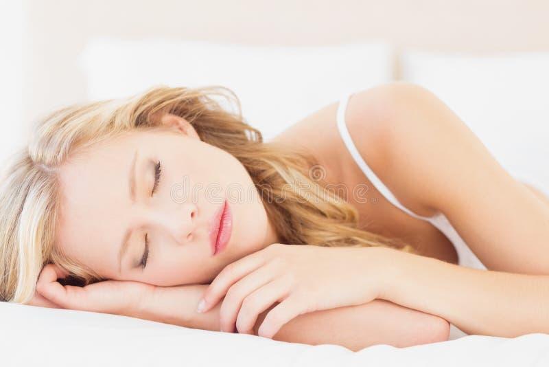 Naturlig ung blondin som sovande ligger på hennes säng royaltyfria foton