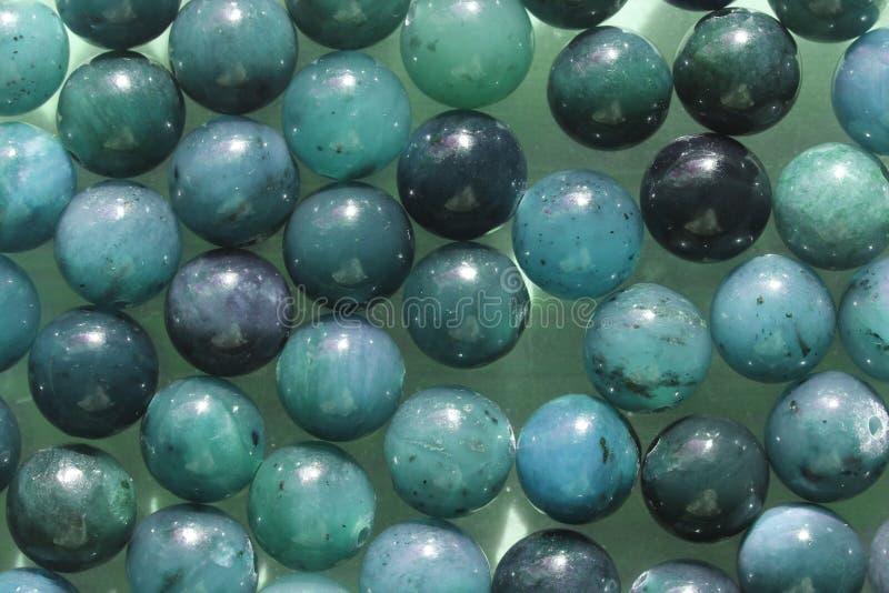 Naturliga blåa mineraliska stenpärlor Blå naturlig bakgrund som göras av rundastenpärlor royaltyfri fotografi