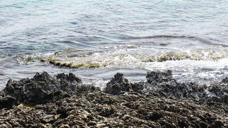 Naturliga blåa svarta stenar för landskaphavshavet seglar utmed kusten royaltyfri bild