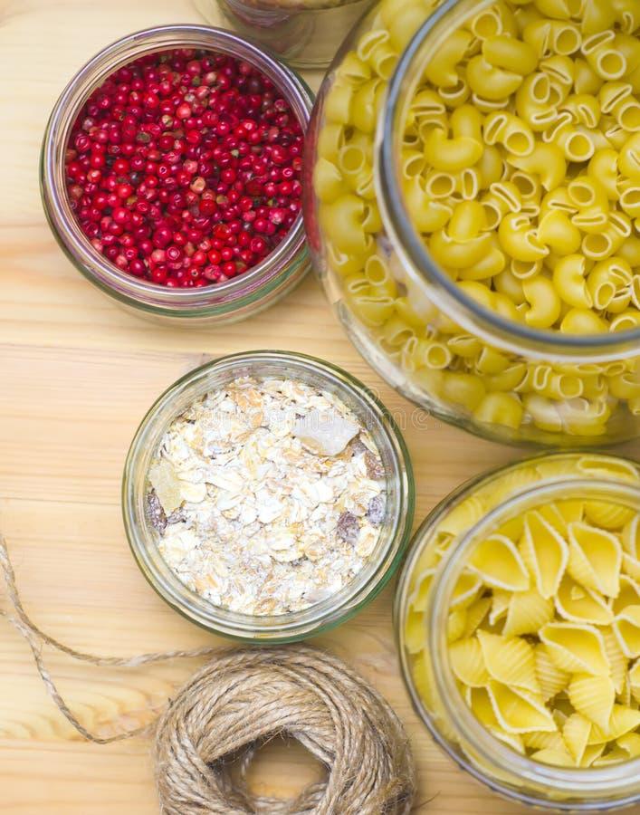 Naturliga f?rpackande exponeringsglaskrus f?r pastaprodukter i stora partier, tankar, selektiv fokus f?r ris royaltyfria foton