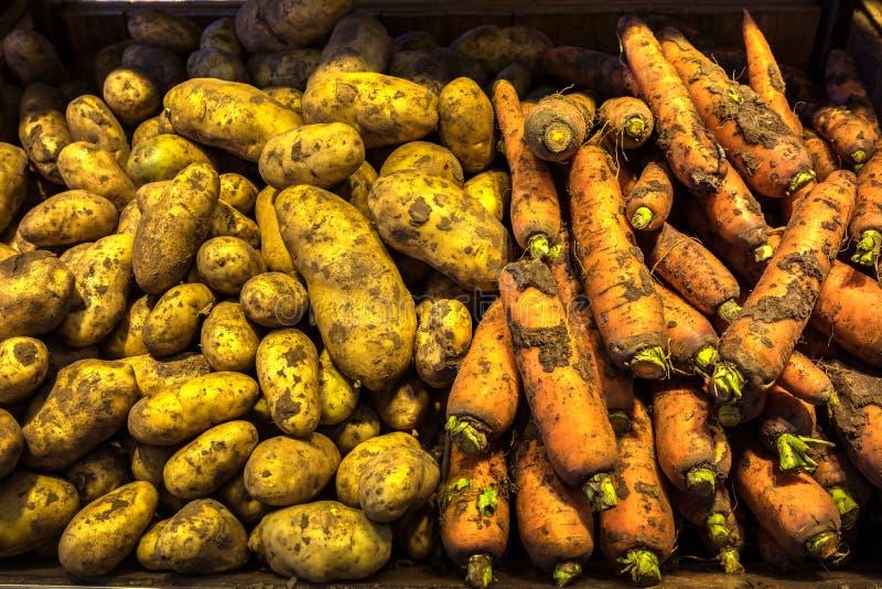 Naturliga grönsaker på marknadsräknare Morötter och potatis arkivbild