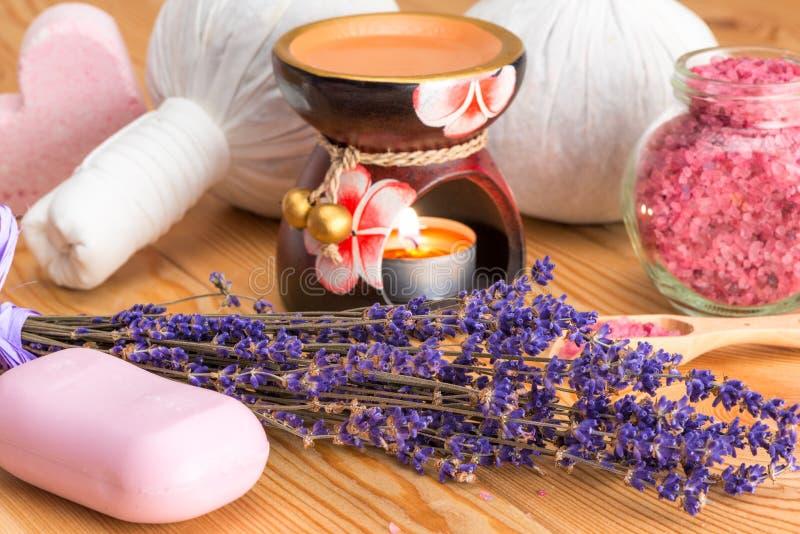 Naturliga lavendelskönhetsmedel för brunnsortbehandlingar och stearinljus i aromlampnärbild royaltyfri fotografi