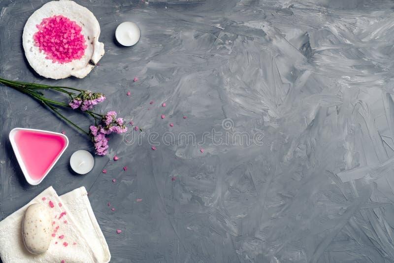 Naturliga organiska skönhetsmedel, steg olja, bad saltar, och rosa blommor på grå färger stenar bakgrund, den bästa sikten, kopie royaltyfria bilder