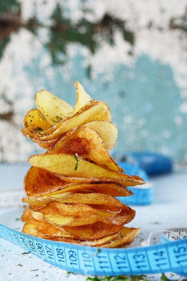 Naturliga potatischiper med havet som är salt på en ljus bakgrund banta royaltyfria bilder