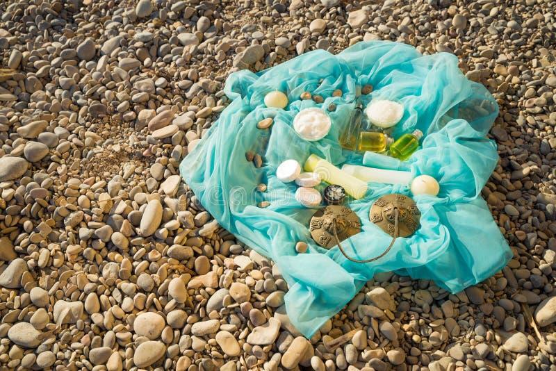Naturliga skönhetsmedel på strandkiselstenar royaltyfri fotografi