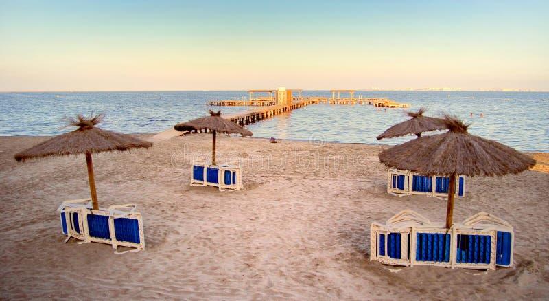 Naturliga sugrörparasoller på en öde strand med stor bryggagoi royaltyfri foto