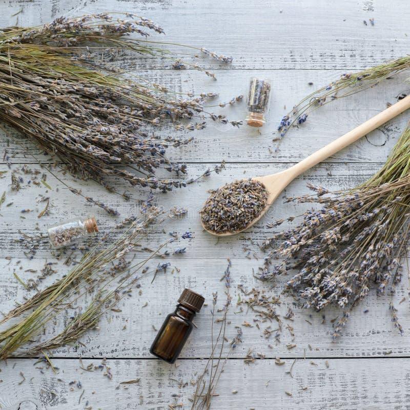 Naturliga torra lavendelblommor med organisk lavendelolja över träbakgrund royaltyfri bild