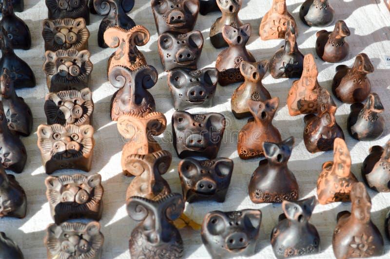 Naturliga traditionella härliga gamla bruna barns för lerakrukmakeri leksaker, visslingar i form av djur, svin, får, fåglar royaltyfri fotografi