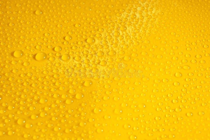 naturliga vattendroppar på gul bakgrundstextur arkivfoton