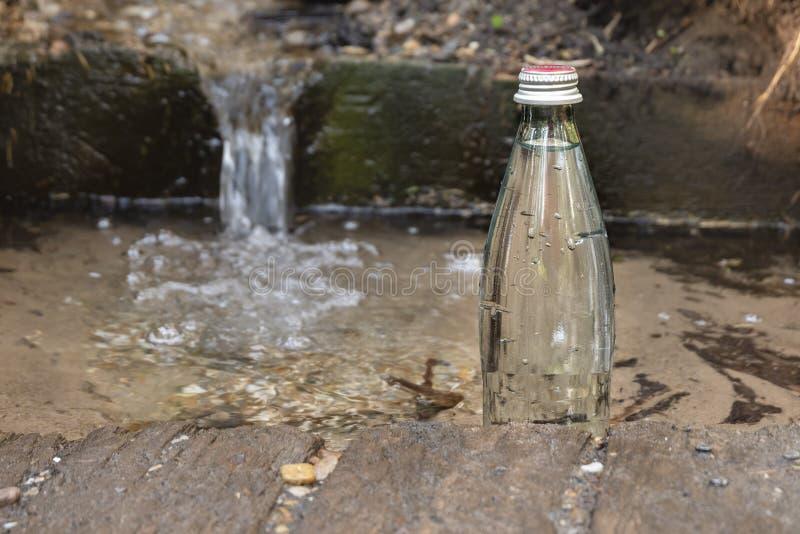 Naturligt ekologiskt v?rvatten Glasflaska med kallt vatten royaltyfri foto