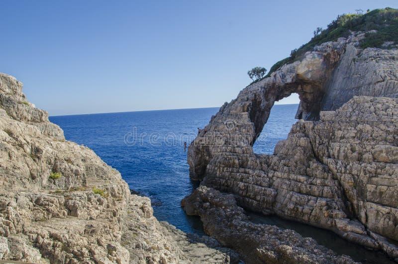 Naturligt f?nster i sten i Korakonissi och folk som hoppar i vattnet fr?n en klippa royaltyfri fotografi