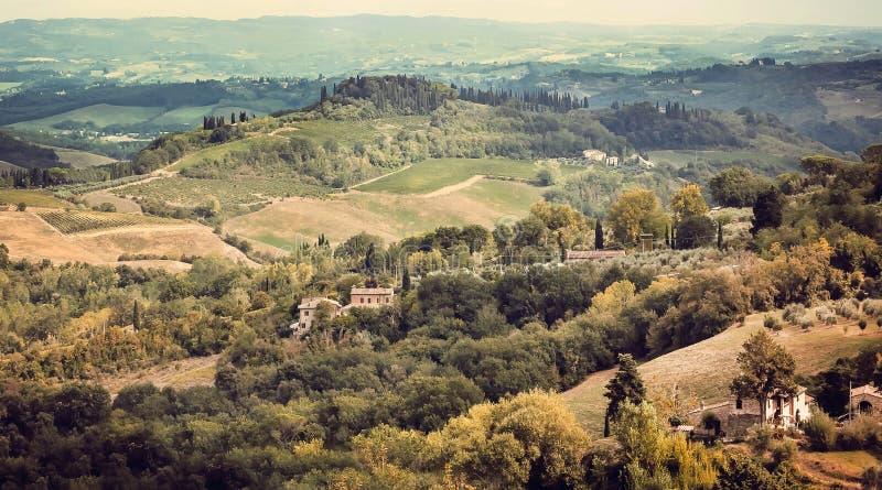 Naturligt landskap av Tuscany med träd, gröna kullar och medeltida byar Italiensk bygd i morgonljus royaltyfri fotografi