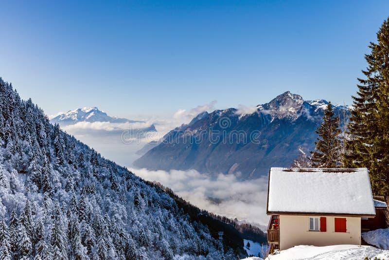 Naturligt landskap med det ensamma huset i snön alpin royaltyfri bild