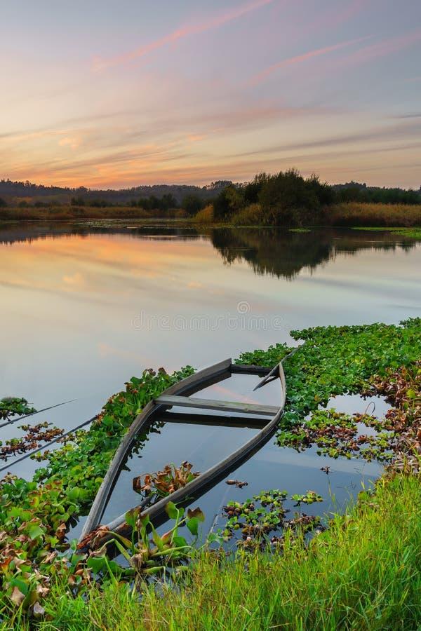 Naturligt landskap med fartyg i vattnet på solnedgången Förbluffa sjön med små artisanal fiskebåtar arkivfoton