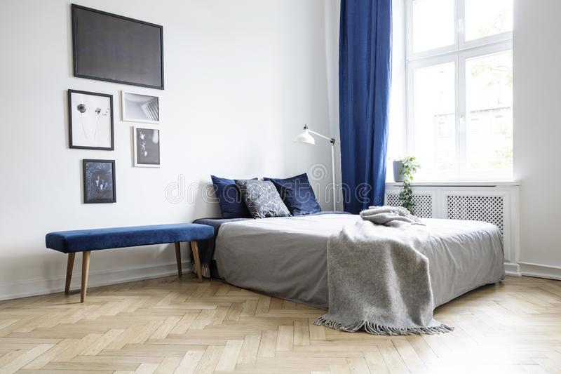 Naturligt ljus som kommer till och med ett stort fönster in i en vit, och marinblå sovruminre med hemtrevlig säng och trägolvet royaltyfria foton