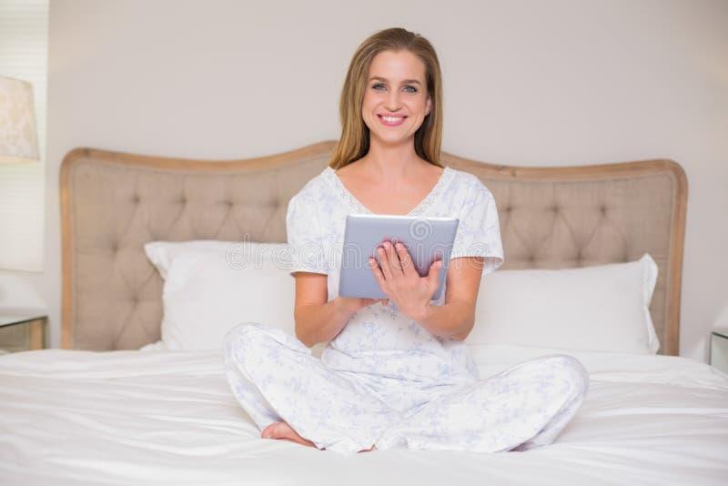 Naturligt lyckligt kvinnasammanträde på säng genom att använda minnestavlan arkivbilder