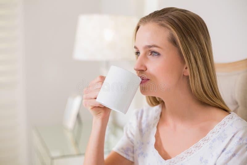 Naturligt nöjt kvinnasammanträde på att dricka för säng royaltyfri fotografi