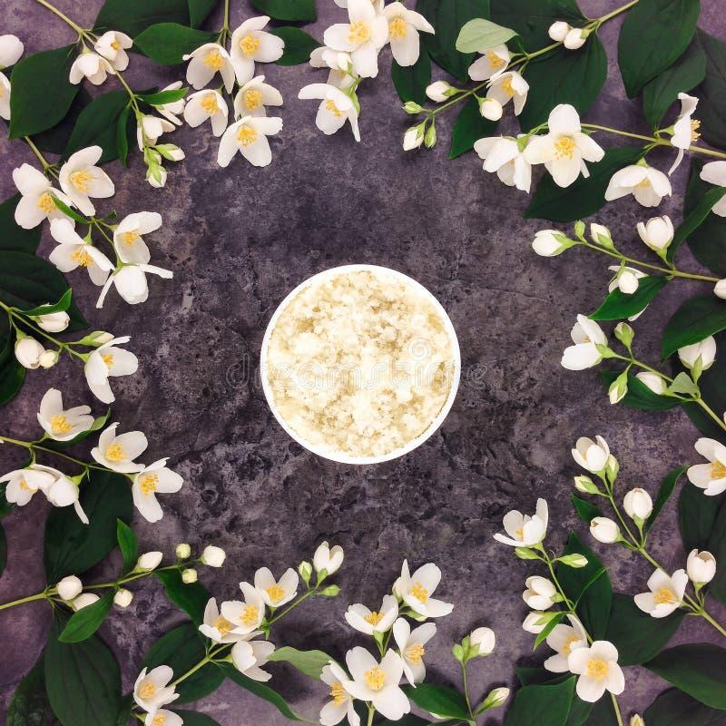 Naturligt skura för brunnsortbehandling, och jasmin blommar på stenbakgrund royaltyfri foto
